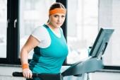 attraktive übergewichtiges Mädchen auf Laufband beim Blick in die Kamera im Fitness-Studio trainieren