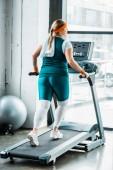 Fotografie übergewichtiges Mädchen mit Handtuch auf den Schultern läuft auf dem Laufband in der Turnhalle