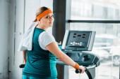 Fotografie Erschöpftes übergewichtiges Mädchen mit Handtuch auf den Schultern blickt in die Kamera auf dem Laufband im Fitnessstudio