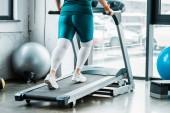 Fotografie Ausgeschnittene Ansicht eines übergewichtigen Mädchens, das in der Turnhalle auf dem Laufband läuft