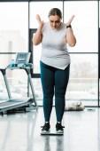 donna in sovrappeso sorpresa gesturing mentre levandosi in piedi sulle scale