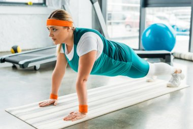 concentrated plus size woman doing plank exercise on fitness mat