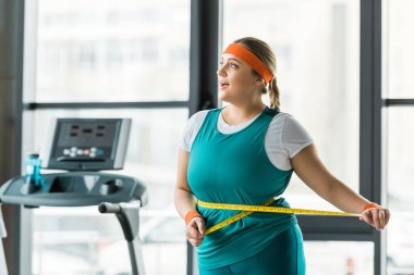 cheerful plus size girl measuring waist in gym
