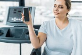 cheerful overweight girl looking at smartphone with blank screen in gym