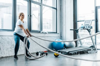 overweight woman training with battle ropes in gym