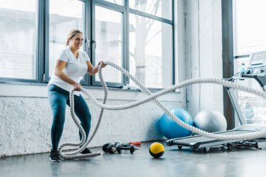 cheerful overweight woman training with battle ropes in gym