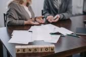 Selektiver Schwerpunkt des Wortes Rente aus Holzklötzen mit Senioren-Paar im Hintergrund