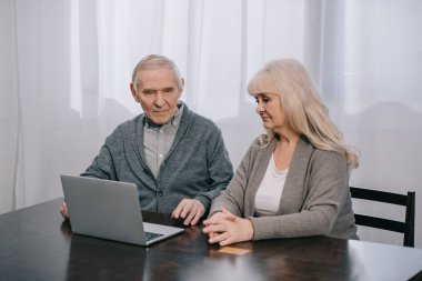 upset senior couple sitting at table and using laptop at home