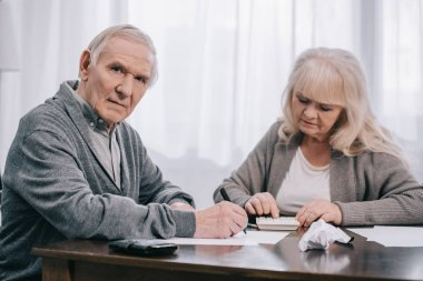 senior coupe sitting at table with paperwork while counting on calculator at home