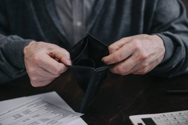 cropped view of senior man holding empty wallet