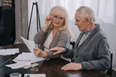 senior couple sitting at table with documents and money