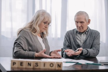 senior couple at table with word 'pension' made of wooden blocks on foreground