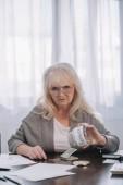 Starší žena při pohledu na fotoaparát a držení sklenice slovem Penzion při počítání peněz