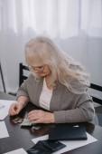 ženské důchodce v brýlích sedí u stolu a počítání peněz doma