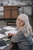 smutná žena důchodce sedí u stolu, při pohledu na fotoaparát a počítání peněz doma