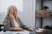 Starší žena sedí u stolu s penězi a papírování při počítání rozpočtu doma