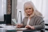 Starší žena sedí u stolu, pomocí kalkulačky a počítání peněz