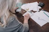 zadní pohled na starší žena sedí u stolu, pomocí kalkulačky a počítání peněz