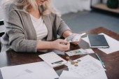 cropped view of senior woman sitting at table with paperwork and counting money