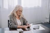 Starší žena sedí u stolu s papíry a počítání peněz