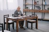 starší muž, sedící u stolu s papíry a použití kalkulačky při počítání peněz v obývacím pokoji