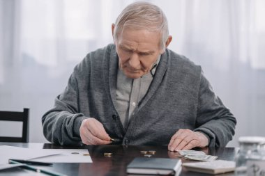 senior man sitting at table and counting money at home