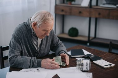 senior man sitting at table with money, paperwork and glass jar with 'pension' lettering