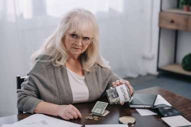 senior woman looking at camera, holding glass jar with 'pension' word and counting money