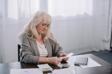 senior woman sitting at table with paperwork and counting money