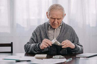 male pensioner sitting at table with paperwork and putting money in wallet