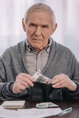 male pensioner sitting at table, looking at camera and putting money in wallet