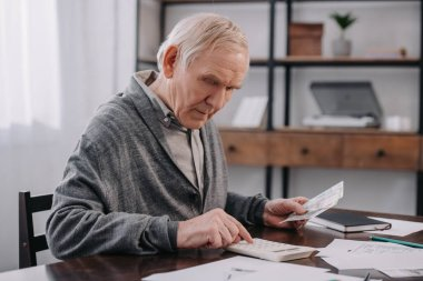 senior man sitting at table with paperwork and using calculator while counting money