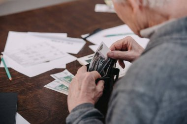 partial view of senior man sitting at table with paperwork and counting money