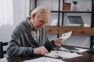 senior man in casual clothes sitting at table with paperwork and using calculator while counting money