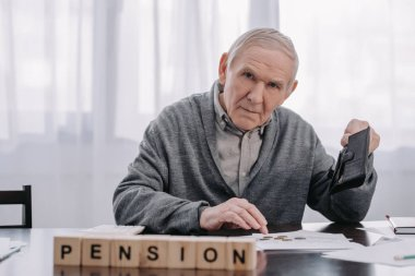 male pensioner with wallet and paperwork sitting at table with word 'pension' made of wooden blocks on foreground