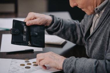 male pensioner sitting at table with paperwork and counting money