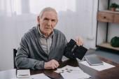 starší muž, sedící u stolu s papíry a podržíte peněženku a počítání peněz doma