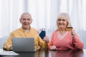 starší pár s letenky, cestovní pasy a kreditní karty sedící u stolu s notebookem a při pohledu na fotoaparát