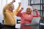 Fotografie glückliches Seniorenpaar in bunten Kleidern, das mit Laptop am Tisch sitzt und mit Händen in der Luft jubelt