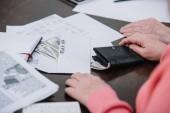 oříznutý pohled starší pár sedí u stolu s papíry, peníze a obálku s nápisem roth ira