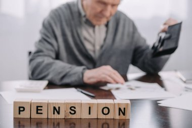 selective focus of word 'pension' made of wooden blocks with male pensioner holding wallet on background