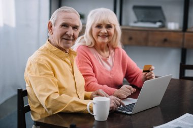 senior couple sitting on couch with laptop and credit card, looking at camera and doing online shopping at home