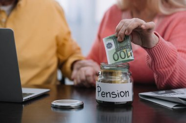 cropped view of senior couple putting money in glass jar with 'pension' word