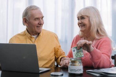 senior couple sitting at table with laptop while woman putting money in glass jar with 'pension' lettering