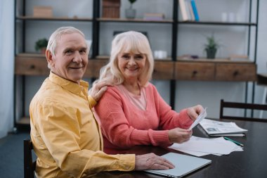 happy senior couple looking at camera while sitting at table with documents