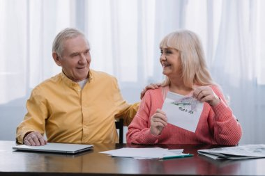 senior couple holding envelope with 'roth ira' lettering and money while sitting at table