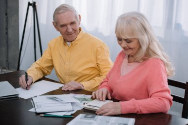 senior coupe sitting at table with calculator and counting money