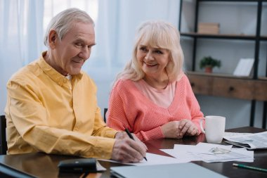 happy senior couple sitting at table and filling documents at home