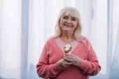 usměvavá starší žena při pohledu na fotoaparát a držení kužel zmrzliny doma