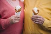oříznutý pohled na starší pár se drží kornouty na zmrzlinu